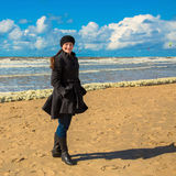 Smiling happy woman dressed in a coat at the beach Stock Photos