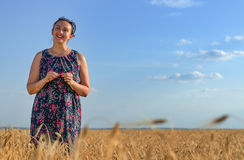 Smiling happy woman in a golden field of wheat Stock Images