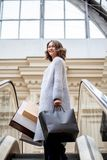 Smiling happy woman in knitted bright summer coat with shopping bags on escalator in city shopping center royalty free stock images