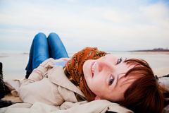 Smiling happy woman lying on the beach Royalty Free Stock Photos