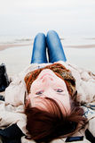 Smiling happy woman lying on the beach Stock Photography