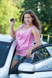 Smiling happy woman with new car and igniton key in hands Royalty Free Stock Image