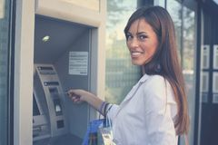 Smiling happy woman with shopping bags at ATM. Looking at camer royalty free stock photos
