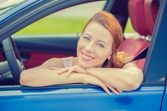 Smiling happy woman sitting in a new blue car Royalty Free Stock Images