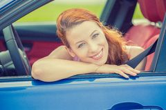 Smiling happy woman sitting in a new blue car Royalty Free Stock Photo