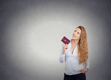 Smiling happy woman standing holding passport looking up imagining new life Stock Image