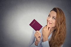 Smiling happy woman standing holding passport looking up imagining new life Stock Photography