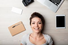 Smiling happy woman surrounded by office supplies royalty free stock image