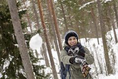 Smiling, happy woman throws a snowball in the winter forest. A smiling, happy woman throws a snowball playfully in the winter forest Stock Photos