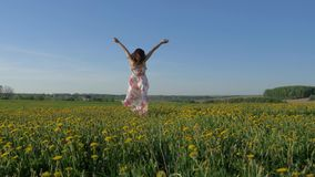 Smiling Happy Woman Walking On A Blooming Yellow Field In A Dress Turning Around