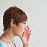 Smiling happy woman whisper, speak, announce, communicate. On plain background, square format Royalty Free Stock Photography