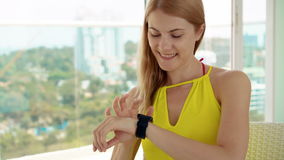 Smiling happy woman in yellow dress sitting on balcony. Using her smartwatch, messaging with friends stock footage