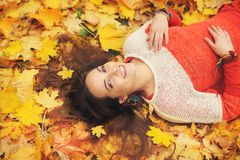 Smiling happy womanl portrait, lying in autumn leaves Stock Photos