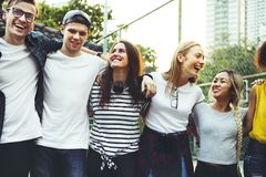 Smiling happy young adult friends arms around shoulder outdoors stock photography