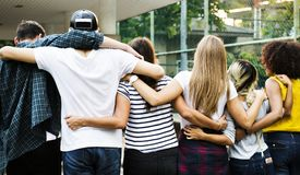Smiling happy young adult friends arms around shoulder outdoors. Friendship and connection concept royalty free stock photo