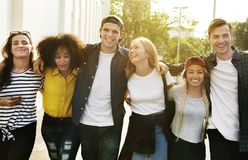 Smiling happy young adult friends arms around shoulder walking o stock images