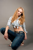 Smiling happy young blonde girl in jeans Stock Photos