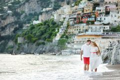 Smiling happy young couple walking on Positano beach Royalty Free Stock Photo