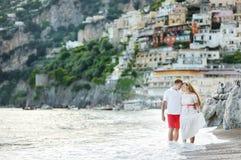 Smiling happy young couple walking on Positano beach. Smiling happy young couple walking on the beach of Positano Royalty Free Stock Photo