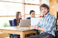Smiling happy young curly male working in team using notebook Royalty Free Stock Photography