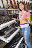 Smiling happy young girl choosing synthesizer Stock Photography
