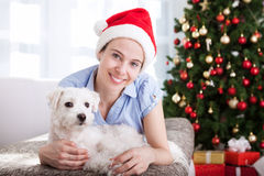 Smiling happy young girl with dog relax at home for christmas ho Stock Photo