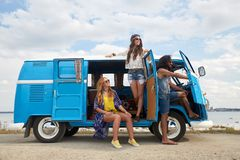 Smiling happy young hippie friends at minivan car Stock Photos