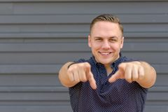 Smiling happy young man pointing to the camera stock image