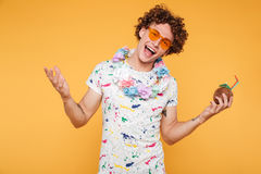 Smiling happy young man in sunglasses and beach wear. Standing isolated over yellow background Stock Image