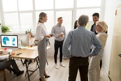 Smiling happy young and senior office workers talking in coworki. Smiling happy young and senior multi-ethnic workers talking in coworking, diverse corporate royalty free stock image