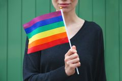 Smiling happy young woman holding lgbt colorful rainbow flag royalty free stock photos