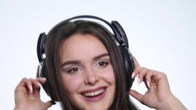 Smiling happy young woman listening to music with earphones and dancing isolated on white background.  stock video footage