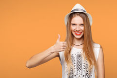 Smiling happy young woman showing thumbs up, isolated on orange background Royalty Free Stock Image