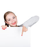 Smiling happy young woman standing behind and leaning on a white blank billboard or placard, expresses different Stock Image