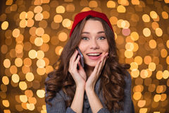Smiling happy young woman talking on smartphone over sparkling background. Smiling happy young woman in red hat and knitted mittens talking on smartphone over Stock Image
