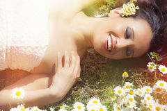 Smiling harmony woman lying on grass with daisies. Lights risers. Beautiful Caucasian woman with a big smile lying on a green lawn embellished. Concept of stock photos