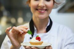 Smiling head chef putting mint leaf on little cake on plate Stock Photos