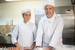 Smiling head chef showing trainee how to prepare dough Royalty Free Stock Images