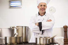 Smiling head chef standing arms crossed behind pot. In professional kitchen stock photos