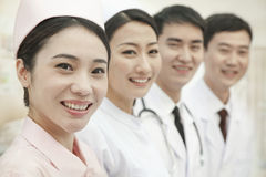 Smiling Healthcare workers standing in a row, looking at camera, China Stock Photo