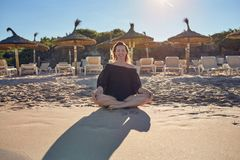 Smiling healthy barefoot woman sitting cross-legged on the beach. As she prepares to meditate against a backdrop of resort beach umbrellas backlit by the Stock Photo