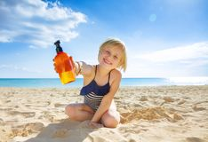 Smiling healthy child in swimwear on seacoast showing lotion. Sun kissed beauty. smiling healthy child in swimwear on the seacoast showing suntan lotion royalty free stock photos