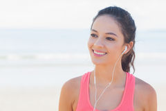 Smiling healthy woman with earphones on beach Stock Photo