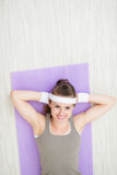 Smiling healthy woman laying on fitness mat Royalty Free Stock Photo