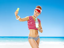 Smiling healthy woman in red sun visor on seashore with cocktail Stock Image
