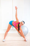 Smiling healthy young girl doing fitness exercises Royalty Free Stock Photos