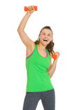 Smiling healthy young woman making exercise with dumbbells Royalty Free Stock Photography