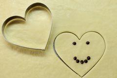 Smiling heart with chocolate eyes and smile with cooking shape heart top view. Romantic concept. Valentines day symbol. Smiling happy face love heart. Romantic Royalty Free Stock Photos
