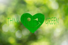 Smiling heart shaped green leaf with text think green on blurred bokeh background. Environment concept Royalty Free Stock Photos