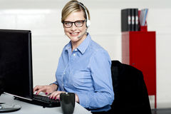 Smiling help desk woman typing on keyboard Stock Photography